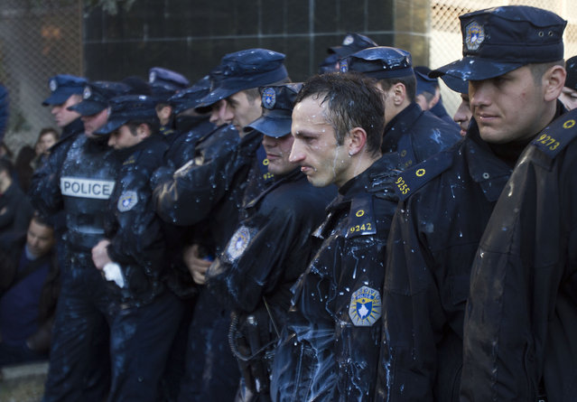 Kosovo police officers react after being sprayed with milk by students, as they prevented them from storming the building of the main public Pristina University on Friday, Feb. 7, 2014. Police in Kosovo used tear gas to disperse hundreds of protesters trying to break through a police cordon and storm the office of the dean of the main public university accused of corruption and mismanagement. Protesters threw stones at police and splashed them with milk and red paint and police used pepper spray. (Photo by Visar Kryeziu/AP Photo)