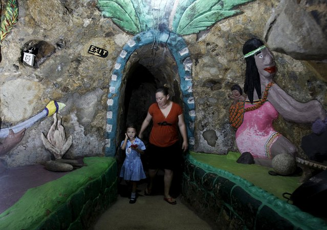 Lidieth Barrantes and her daughter walk in a hallway of a house built underground by Manuel Barrantes in San Isidro de Perez Zeledon, Costa Rica, March 14, 2016. (Photo by Juan Carlos Ulate/Reuters)
