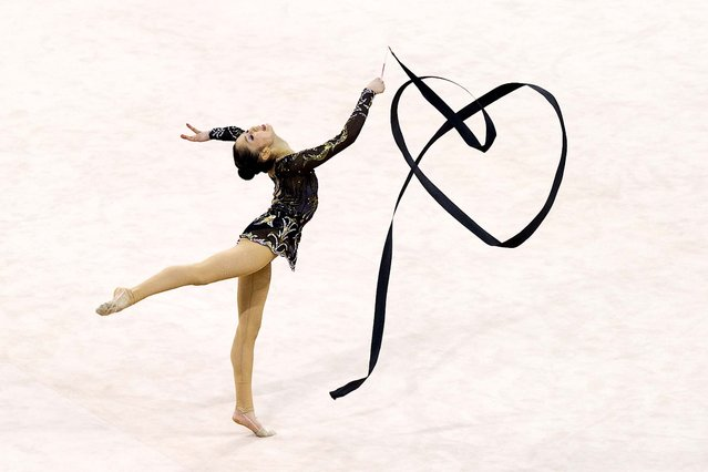 Riko Anakuba of Japan makes the shape of a heart during her performance at the rhythmic gymnastics individual all-around qualification & team final rotation during the 16th Asian Games in 2010. (Photo by Nicolas Asfouri/AFP Photo)