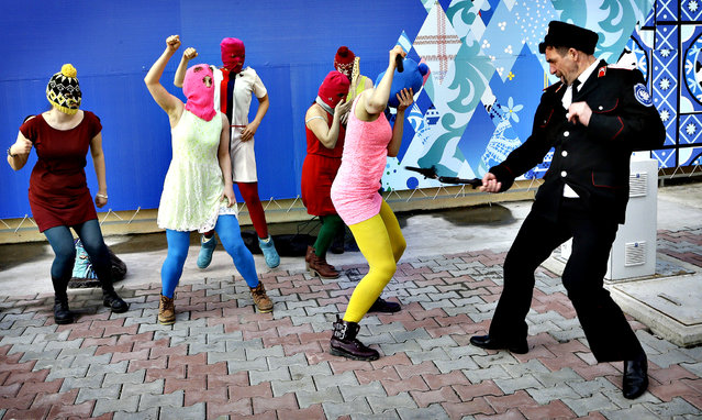 A Cossack militiaman attacks Nadezhda Tolokonnikova as she and fellow members of the punk group p*ssy Riot, including Maria Alekhina, center, in the pink balaclava, stage a protest performance in Sochi, Russia, on Wednesday, February 19, 2014.(Photo by Morry Gash/AP Photo)