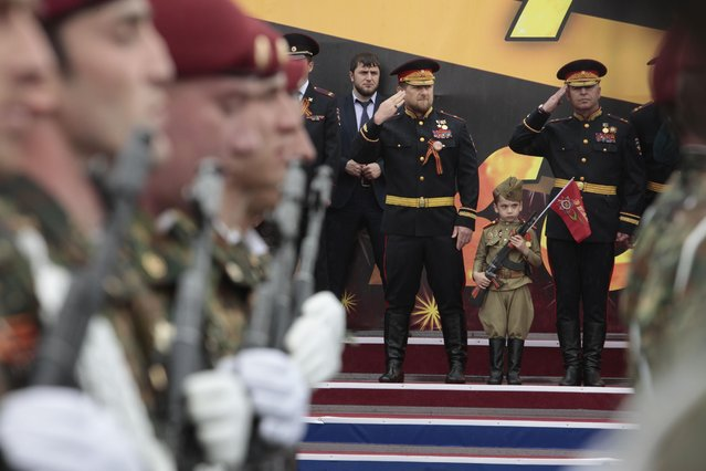 Chechen regional leader Ramzan Kadyrov, rear left, wearing a Russian military uniform, salutes during celebrations marking the 70th anniversary of the victory over Nazi Germany, in Chechnya's provincial capital Grozny, Russia, Saturday, May 9, 2015. (Photo by Musa Sadulayev/AP Photo)