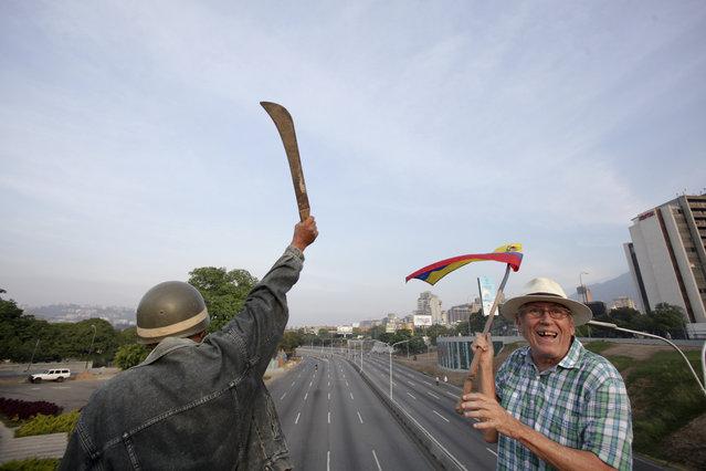 An opponent of Venezuela's President Nicolas Maduro raises a machete during an attempted military uprising outside the La Carlota airbase in Caracas, Venezuela, Tuesday, April 30, 2019. (Photo by Boris Vergara/AP Photo)