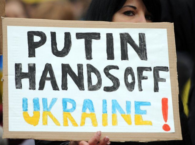 "A demonstrator holds a poster reading ""Putin, Hands off Ukraine"" during a demonstration in front of the Russian embassy in Berlin, Germany Sunday March 2, 2014. (Photo by Britta Pedersen/AP Photo/DPA)"