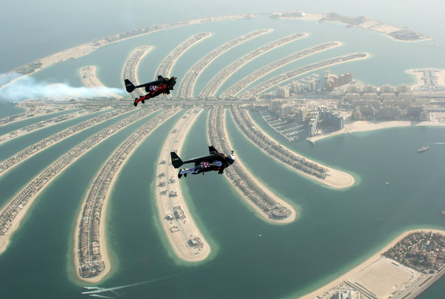 An aerial view taken from a sea plane shows Swiss pilot and original Jetman Yves Rossy (front) and Vince Reffett flying over Dubai's Palm Island, Dubai, United Arab Emirates May 12, 2015. (Photo by Lara Sukhtian/Reuters)