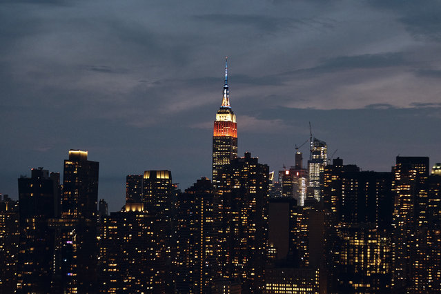The top of the Empire State Building is lit in red, white and blue before the Fourth of July fireworks show, Wednesday, July 4, 2018, in New York. (Photo by Andres Kudacki/AP Photo)