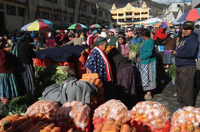 Maria Isabel Luna, 75, wears an American towel for warmth over her traditional Mayan dress while working at a vegetable market on February 11, 2017 in Almolonga, Guatemala.  She said that two of her family members work as immigrant laborers in Los Angeles. The Mayan town in the western highlands district of Quetzaltenango has surged in prosperity in recent years with high-productivity vegetable farming, exporting much of its excess crops to neighborning El Salvador. (Photo by John Moore/Getty Images)