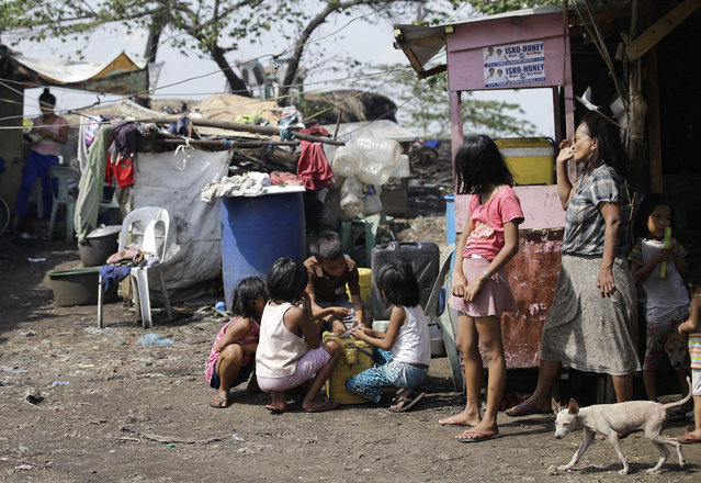 In this Thursday, May 9, 2019 photo, Agnes Veles, right, watches as children count their day's earning from selling ice candy outside their shanty at Manila's former dumpsite Smokey Mountain, Philippines. (Photo by Aaron Favila/AP Photo)
