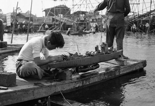 A movie studio workman rigs up one of the scale model warships used in filming a battle scene in a Japanese documentary that tells the story of the last day of the battleship Yamato, on June 8, 1953. (Photo by Yuichi Ishizaki/AP Photo via The Atlantic)