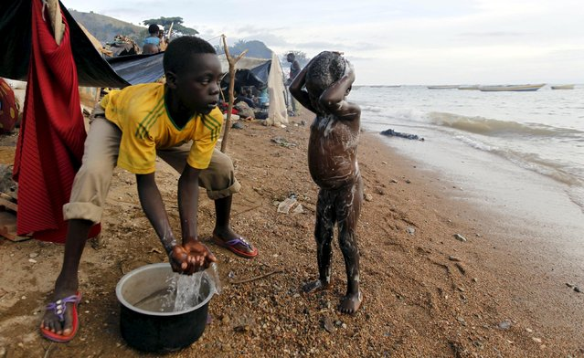 A Burundian refugee washes his kin as they gather on the shores of Lake Tanganyika in Kagunga village in Kigoma region in western Tanzania, to wait for MV Liemba to transport them to Kigoma township, May 17, 2015. (Photo by Thomas Mukoya/Reuters)