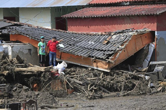 Residents stand in front of damaged houses after a landslide sent mud and water crashing onto homes close to the municipality of Salgar in Antioquia department, Colombia May 19, 2015. (Photo by Jose Miguel Gomez/Reuters)