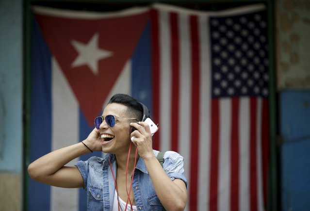 "Jurangel, 25, a dancer, poses for a photograph in front of the Cuban and U.S. flags in Havana, March 25, 2016. Regarding Obama's historic visit to the island, Jurangel said ""Spectacular"". (Photo by Ueslei Marcelino/Reuters)"