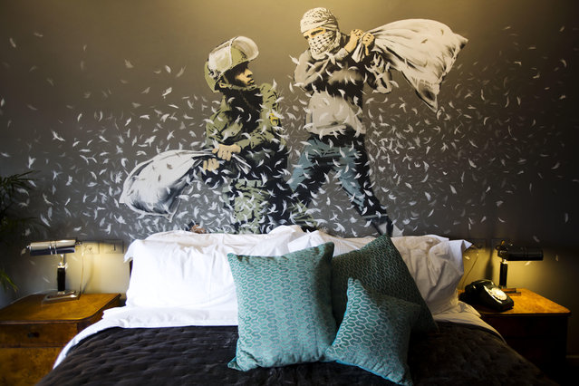 "A Banksy wall painting showing Israeli border policeman and Palestinian in a pillow fight is seen in one of the rooms of the ""The Walled Off Hotel"" in the West Bank city of Bethlehem, Friday, March 3, 2017. The owner of a guest house packed with the elusive artist Banksy's work has opened the doors of his West Bank establishments to media, showcasing its unique ""worst view in the world"". The hotel, several of whose rooms look onto an Israeli security watchtower, is awash in the trademark satirical work of the mysterious artist. The highlight is room number three, known as ""Banksy's Room"", where guests sleep in a king-size bed underneath Banksy's artwork showing a Palestinian and an Israeli in a pillow fight. The hotel also features a presidential suite and a museum with the artist's politically-charged work. It has the markings of a gentleman's club from the English colonial period. The entrance to one small niche accommodates a life-size figure of Arthur James Balfour signing his 1917 letter that came to be known as the Balfour declaration, and was the basis for the international push for the creation of Israel. The cheapest rooms were available from $30 a night. The nine-room hotel named ""The Walled Off Hotel"" will officially open on March 11. (Photo by Dusan Vranic/AP Photo)"