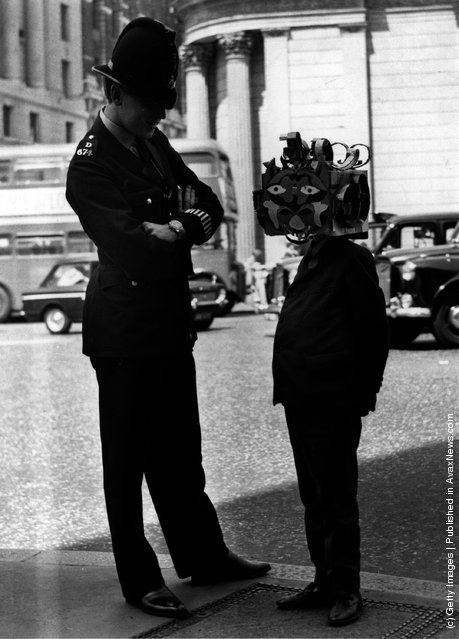A boy wearing an 'Apollo' space mask seen here greeting a policeman, 1969