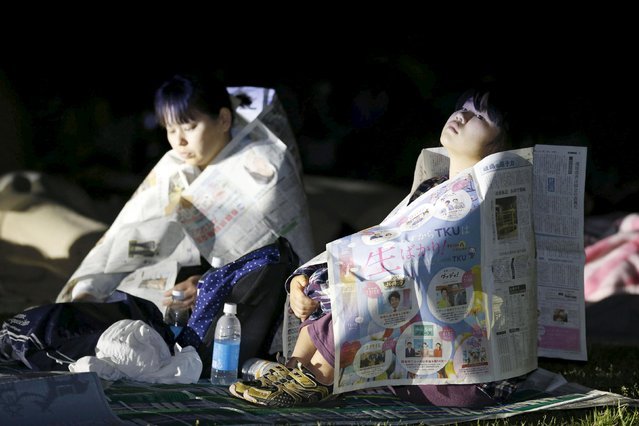 Evacuees use newspapers to warm themselves at Prefectural University of Kumamoto after an earthquake in Kumamoto, southern Japan, in this photo taken by Kyodo April 16, 2016. (Photo by Reuters/Kyodo News)