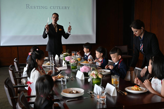 """This picture taken on June 1, 2019 shows Guillaume de Bernadac teaching children how to use cutlery during an etiquette and manners class in central Shanghai. Against a soundtrack of classical music, children learn social skills, dining manners and deportment in the class, which costs $390 for four hours of practical instruction per student. Other exercises include how to introduce themselves and greet people, including """"air kisses"""", and even what topics are appropriate to discuss at the dinner table. (Photo by Hector Retamal/AFP Photo)"""