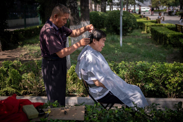 A man gets his hair cut on a street in Beijing on July 8, 2019. (Photo by Nicolas Asfouri/AFP Photo)