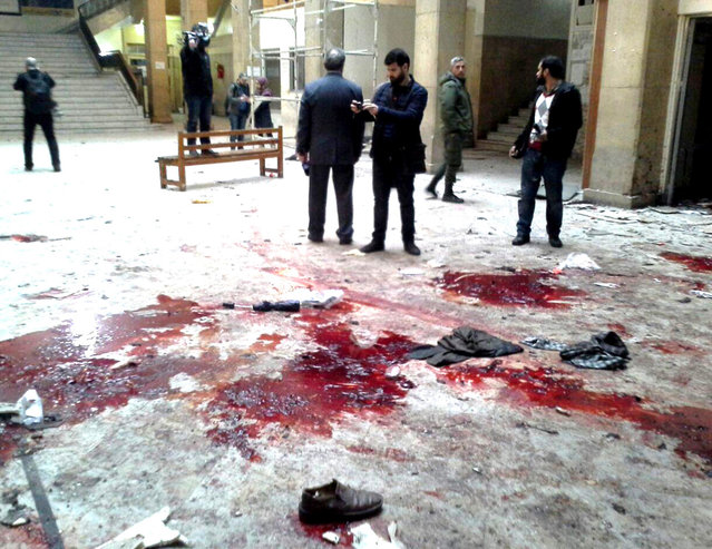 In this photo released by the Syrian official news agency SANA, journalists gather next of blood inside the main judicial building which attacked by a suicide bomber, in Damascus, Syria, Wednesday, March 15, 2017. (Photo by SANA via AP Photo)