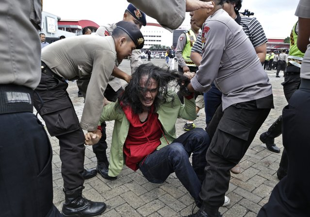 Indonesian students clash with police officers during an anti-tobacco protest outside the venue of the World Tobacco Process and Machinery Exhibition Asia 2016 in Jakarta, Indonesia, 27 April 2016. At least a hundred students staged a rally demanding the government to stop the exhibition, saying that it promotes smoking among youth and children. Indonesia ranks third in the world for the number of smokers after China and India, according to the World Health Organization. (Photo by Mast Irham/EPA)