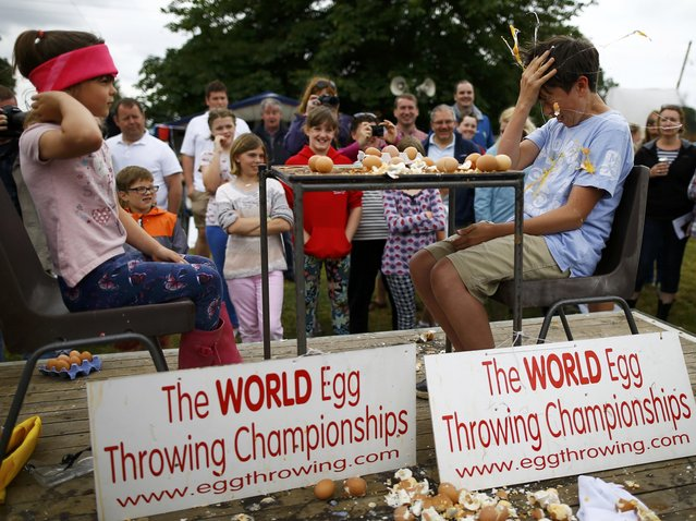 A boy loses in a game of Russian Egg Roulette during the World Egg Throwing Championships and Vintage Day in Swaton, Britain June 28, 2015. (Photo by Darren Staples/Reuters)
