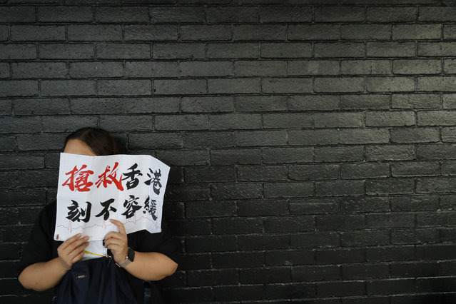 """A woman holds up a sign that reads: """"Rescue Hong Kong, There is no time for delay"""" during a demonstration in Hong Kong Friday, August 2, 2019. Two demonstrations by civil servants and workers in the medical and health care sector were also planned for Friday evening. (Photo by Vincent Thian/AP Photo)"""