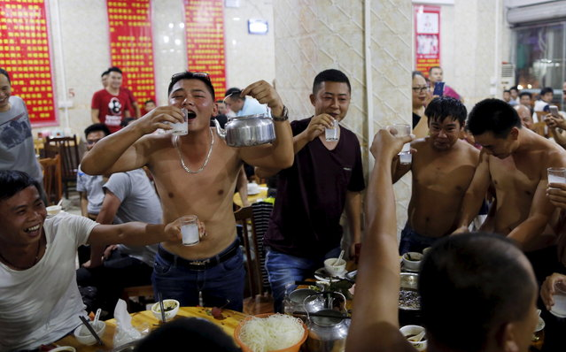 Customers drink over dog meat dishes as they have a gathering to eat dog meat and lychees for celebrating the upcoming local dog meat festival at a dog meat restaurant in Yulin, Guangxi Autonomous Region, June 21, 2015. Local residents in Yulin host small gatherings to consume dog meat and lychees during the festival, which falls on Monday this year, in celebration of the summer solstice which marks the coming of the hottest days. (Photo by Kim Kyung-Hoon/Reuters)
