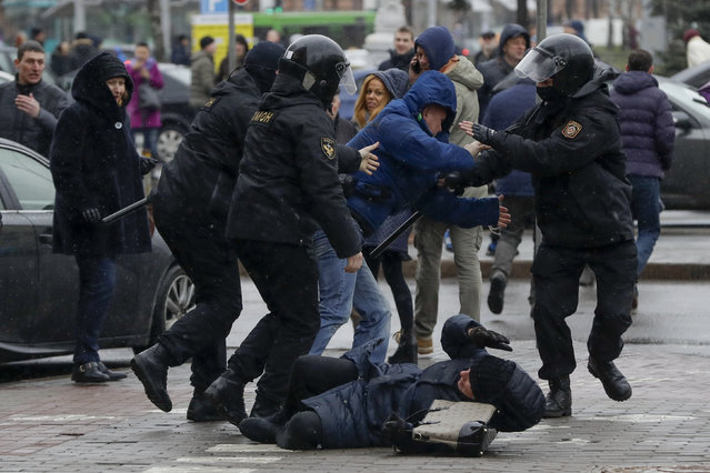 A woman, pushed to the ground by Belarus police tries to defends herself as the police detain an activist during an opposition rally in Minsk, Belarus, Saturday, March 25, 2017. (Photo by Sergei Grits/AP Photo)