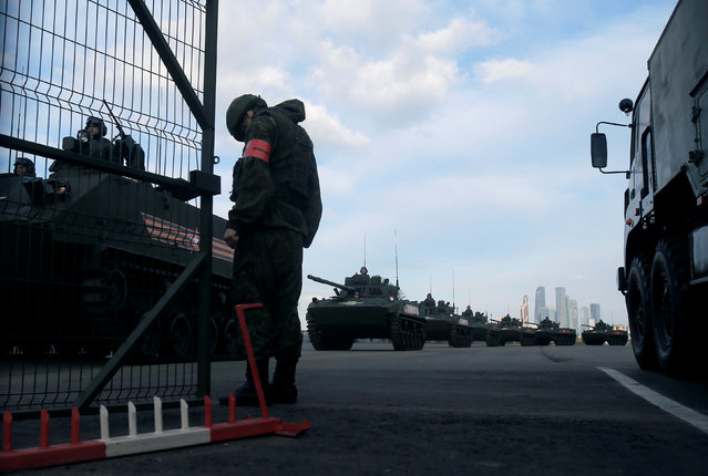 """A Russian military vehicle column is seen before a rehearsal for the Victory Day parade, with the Moscow International Business Center also known as """"Moskva-City"""" seen in the background, at a range in Moscow, Russia, May 5, 2016. (Photo by Maxim Shemetov/Reuters)"""