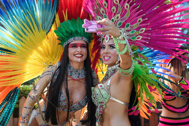 Dancers take a selfie as they wait to perform during the the Notting Hill Carnival in west London, Monday August 26, 2019. (Photo by London News Pictures)
