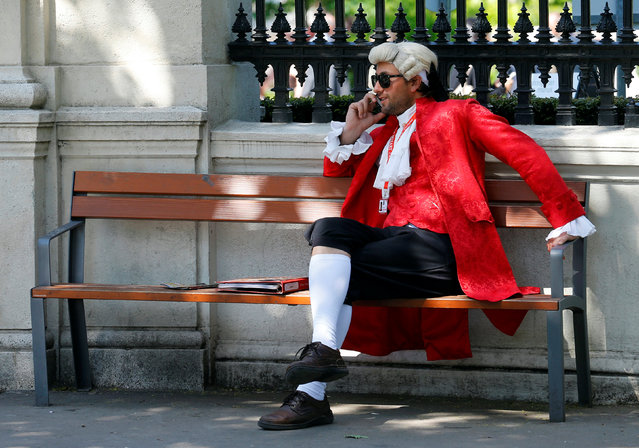 A concert ticket vendor dressed in a historic costume sits on a bench while making a phone call in Vienna, Austria, May 6, 2016. (Photo by Heinz-Peter Bader/Reuters)