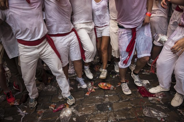 """Revelers walks on the street while celebrate during the launch of the """"Chupinazo"""" rocket, to celebrate the official opening of the 2015 San Fermin Fiestas, in Pamplona, northern Spain, Monday, July 6, 2015. (Photo by Alvaro Barrientos/AP Photo)"""