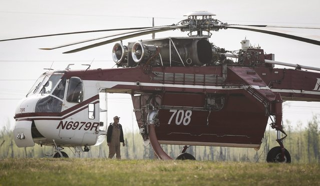 Crew members of a heavy lift helicopter helping with the Fort McMurray wildfire stand by their helicopter at a staging base near Conklin, Alberta, Saturday, May 7, 2016. Canadian officials feared the massive wildfire could double in size by the end of Saturday as they continue to evacuate residents of fire-ravaged Fort McMurray from work camps north of Alberta's oil sands city. (Photo by Jeff McIntosh/The Canadian Press via AP Photo)