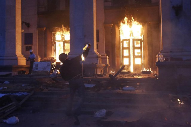A protester throws a petrol bomb at the trade union building in Odessa May 2, 2014. (Photo by Yevgeny Volokin/Reuters)