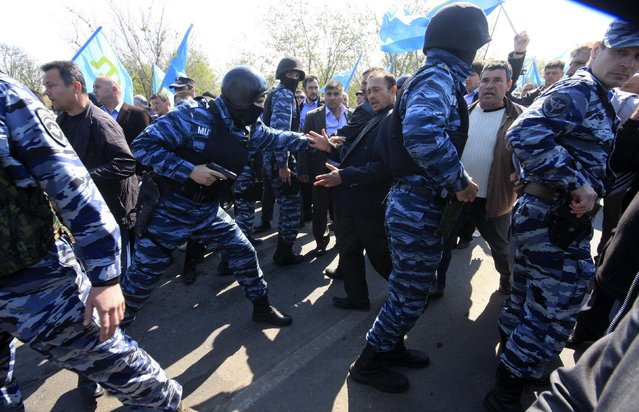 Members of the Russian Interior Ministry security forces attempt to block the way for Crimean Tatars who cross a checkpoint connecting Crimea and Kherson region, to meet with former chairman of the Mejlis of the Crimean Tatars Mustafa Dzhemilev, near the city of Armyansk May 3, 2014. Crimea's Tatar community assembly accused Russia on April 22 of barring its leading political figure from returning to the peninsula following its annexation by Moscow. (Photo by Reuters/Stringer)