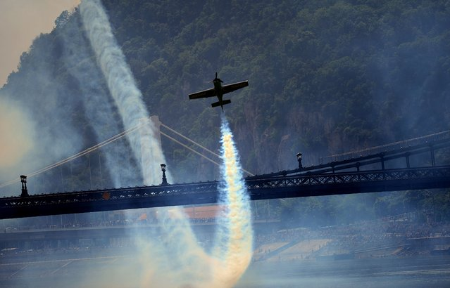 "Hungarian pilot and European champion Zoltan Veres flies under the oldest Hungarian bridge, the ""Lanchid"" (Chain Bridge) with his ""MXS"" type plane on May 1, 2014 during a Red Bull flying and car show around the Danube River of Budapest downtown. (Photo by Attila Kisbenedek/AFP Photo)"