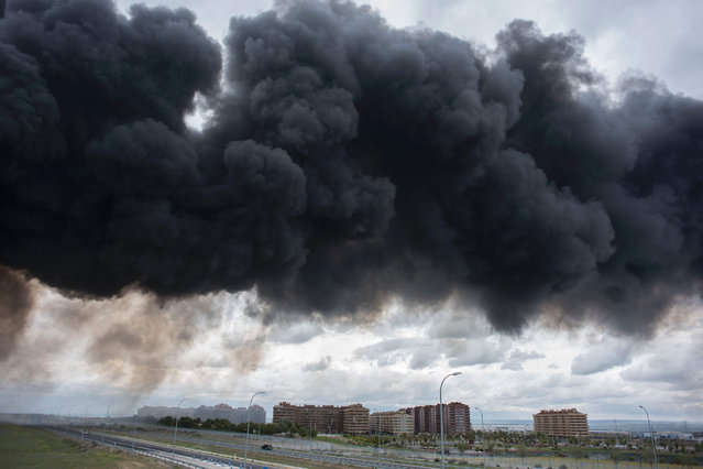 Black clouds of smoke are produced by tyres burning in an uncontrolled dump near the town of Sesena, after a fire brokeout early on May 13, 2016. (Photo by Pedro Armestre/AFP Photo)