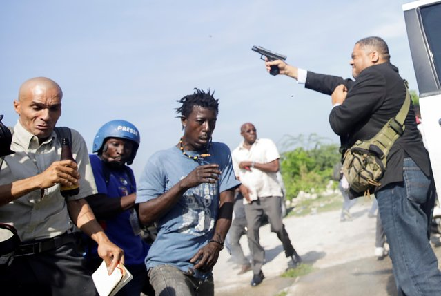 People run as Haiti's Senator Jean Marie Ralph Fethiere (PHTK) fires a gun in the air, injuring Chery Dieu-Nalio, a photographer for Associated Press, while facing opposition supporters in the parking lot of the Haitian Parliament and Senate, as the government attempted to confirm the appointment of nominated Prime Minister Fritz William Michel, in Port-au-Prince, Haiti on September 23, 2019. (Photo by Andres Martinez Casares/Reuters)