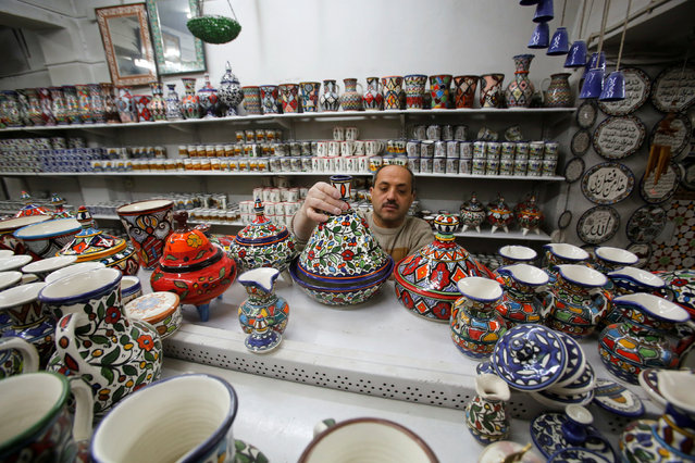A Palestinian man arranges ceramics in Al-Okhowa pottery shop in the West Bank city of Hebron February 9, 2017. (Photo by Mussa Qawasma/Reuters)