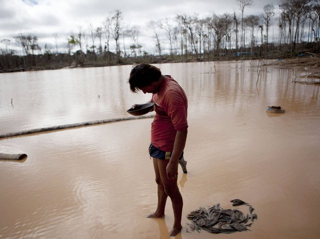 A miner roughly estimates his handful of gold he mined, after working for over 24-hours in La Pampa in Peru's Madre de Dios region. (Photo by Rodrigo Abd/AP Photo)