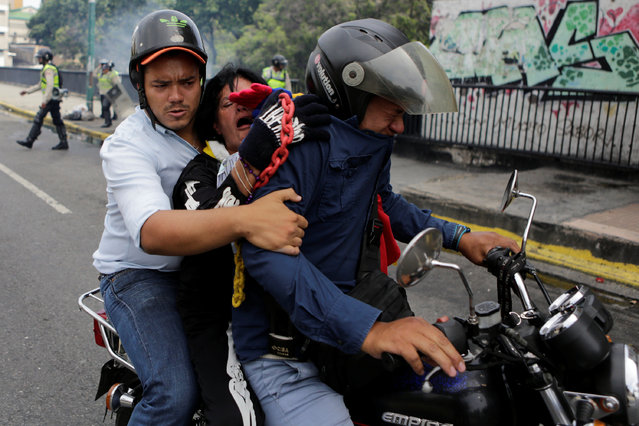 Opposition supporters affected by tear gas try to leave on a motorcycle during clashes with riot policemen during a rally demanding a referendum to remove Venezuela's President Nicolas Maduro in Caracas, Venezuela, May 18, 2016. (Photo by Marco Bello/Reuters)