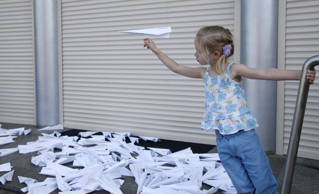 A girl launches a self-made paper plane outside the Dutch embassy as people gather to commemorate the victims of the Malaysia Airlines flight MH17 plane crash a year ago in Kiev, Ukraine, July 17, 2015. (Photo by Valentyn Ogirenko/Reuters)