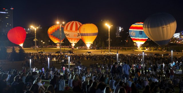 """People look at hot air balloons at the Cup Hot Air event during the Air Sports festival titled """"70 Years of Peaceful Sky"""" in Minsk, Belarus July 18, 2015. (Photo by Vasily Fedosenko/Reuters)"""