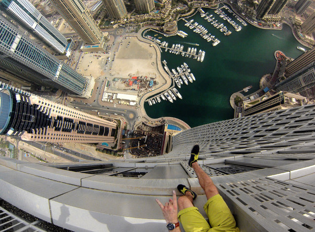 One of the Daredevils legs dangling from a building in Dubai. (Photo by Alexander Remnev/Caters News)