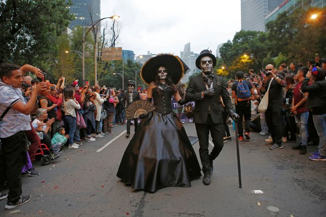 People dressed as Catrinas parade down Mexico City's iconic Reforma avenue during celebrations for the Day of the Dead in Mexico, Saturday, October 26, 2019. (Photo by Ginnette Riquelme/AP Photo)