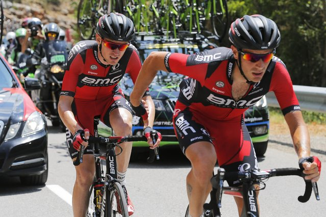 A teammate helps Tejay van Garderen of the U.S., left, after he fell ill during the seventeenth stage of the Tour de France cycling race over 161 kilometers (100 miles) with start in Digne-les-Bains and finish in Pra Loup, France, Wednesday, July 22, 2015. Van Garderen subsequently abandoned the race. (Photo by Christophe Ena/AP Photo)