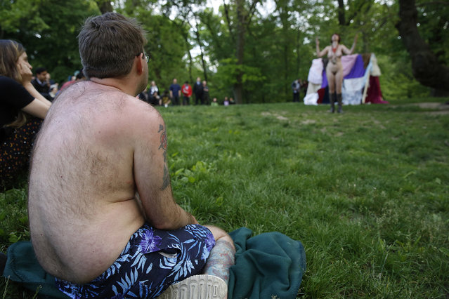 "A spectator wearing a bathing suit watches Gina Marie Russell, far right, as the sorcerer ""Prospero"" perform fully nude during the second scene of the Outdoor Co-Ed Topless Pulp Fiction Appreciation Society's all-female production of Shakespeare's ""The Tempest"", in Central Park, Thursday, May 19, 2016, in New York. The play, which was staged at Summit Rock, Central Park's highest elevation, features 13 female actors, dancers, and musicians. According to the group's website, it's a ""stripped-down production"" in two senses, celebrating body freedom and free expression, with an abridged script in two scenes. (Photo by Kathy Willens/AP Photo)"