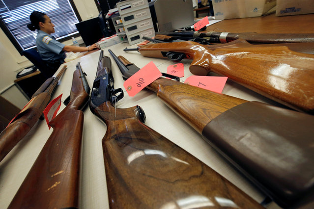 "A Chicago Police officer inventories guns turned in by the public as part of a ""Gun Turn-in"" event where a $100 gift card is given for every firearm and a $10 gift card for each BB-gun, air-gun, or replica firearm turned over to police at Universal Missionary Baptist Church in Chicago, Illinois, U.S. May 28, 2016. (Photo by Jim Young/Reuters)"