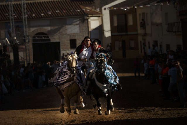 Riders on horse backs embrace each other as they gallop through the town square, on the feast day of Santiago, the patron saint of Spain, during the ancestral festivities of Carpio de Tajo, central Spain, Saturday, July 25, 2015. (Photo by Daniel Ochoa de Olza/AP Photo)