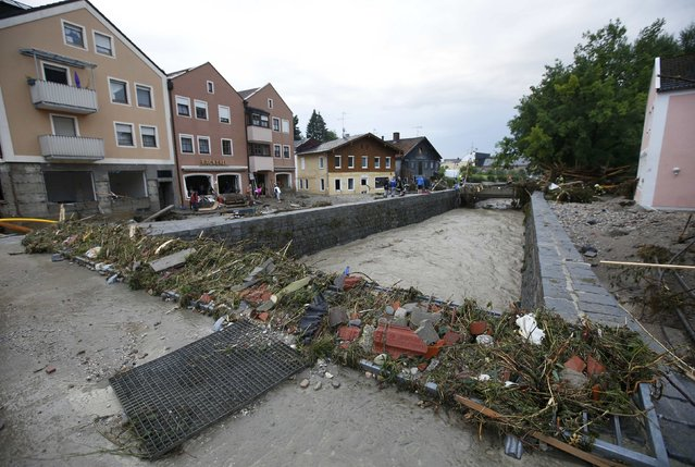 People stand at the bank of river Inn in the flooded Bavarian village of Simbach am Inn east of Munich, Germany, June 1, 2016. (Photo by Michaela Rehle/Reuters)