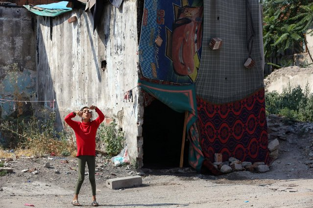 A Syrian refugee girl stands next to her makeshift shelter in Haci Bayram neighborhood in Ankara, Turkey, Monday, July 27, 2015. (Photo by Burhan Ozbilici/AP Photo)