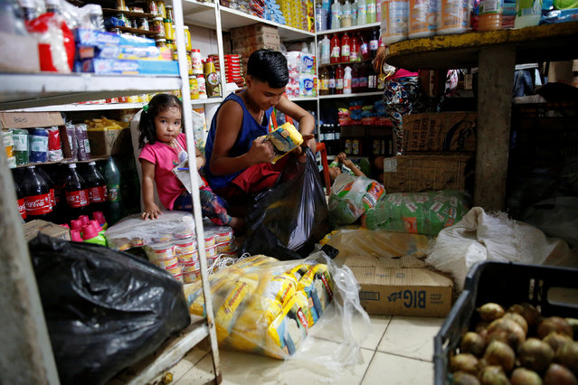 A boy puts packets of corn flour that are made in Colombia in a plastic bag, at a stall that sells food and staple items at a market in La Fria, Venezuela, June 2, 2016. (Photo by Carlos Garcia Rawlins/Reuters)